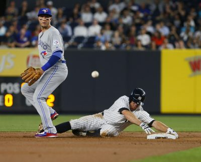 Sep 7, 2016; Bronx, NY, USA; Toronto Blue Jays shortstop Troy Tulowitzki (2) watches the ball as New York Yankees left fielder Brett Gardner (11) is safe at second base after a throwing error in the first inning at Yankee Stadium. Mandatory Credit: Noah K. Murray-USA TODAY Sports