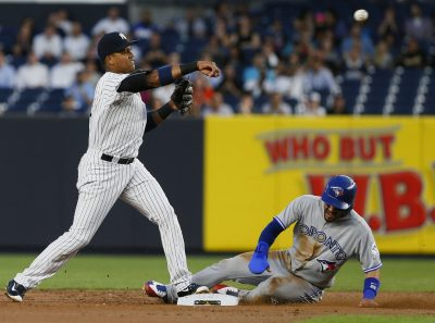 Sep 7, 2016; Bronx, NY, USA; New York Yankees second baseman Starlin Castro (14) makes the throw to first to complete the double over Toronto Blue Jays second baseman Devon Travis (29) in the first inning at Yankee Stadium. Mandatory Credit: Noah K. Murray-USA TODAY Sports