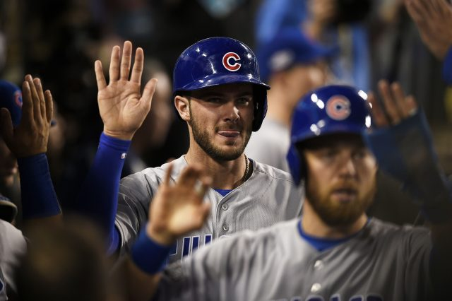 Oct 20, 2016; Los Angeles, CA, USA; Chicago Cubs third baseman Kris Bryant (17) celebrates in the dugout with teammates after scoring a run against the Los Angeles Dodgers in the eighth inning of game five of the 2016 NLCS playoff baseball series against the Los Angeles Dodgers at Dodger Stadium. Mandatory Credit: Kelvin Kuo-USA TODAY Sports