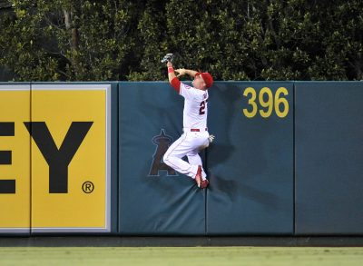 September 26, 2015; Anaheim, CA, USA; Los Angeles Angels center fielder Mike Trout (27) climbs the fence in the fourth inning to catch a fly ball hit by Seattle Mariners first baseman Jesus Montero (not pictured) at Angel Stadium of Anaheim. Mandatory Credit: Gary A. Vasquez-USA TODAY Sports