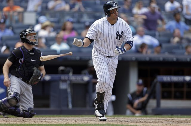 Jun 22, 2016; Bronx, NY, USA; New York Yankees right fielder Carlos Beltran (36) hits a three run home run in front of Colorado Rockies catcher Nick Hundley (4) during the seventh inning of their inter-league game at Yankee Stadium. Mandatory Credit: Adam Hunger-USA TODAY Sports