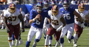 New York Giants quarterback Daniel Jones, second from left, runs the ball during the first half of an NFL football game against the Washington Redskins, Sunday, Sept. 29, 2019, in East Rutherford, N.J.