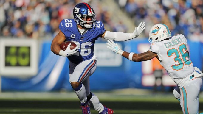 New York Giants running back Saquon Barkley (26) runs past Miami Dolphins free safety Adrian Colbert (36) during the first half of an NFL football game, Sunday, Dec. 15, 2019, in East Rutherford, N.J.