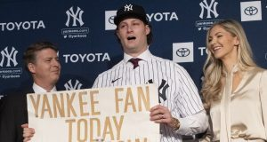 New York Yankees pitcher Gerrit Cole, center, holds a sign he used as a young Yankees fan, as he is introduced as the baseball clubs newest player during a baseball media availability, Wednesday, Dec. 18, 2019 in New York. He is joined by team owner Hal Steinbrenner, left, and his wife, Amy Cole.