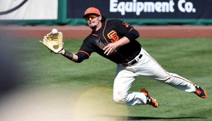 SCOTTSDALE, AZ - FEBRUARY 26: Jarrett Parker #6 of the San Francisco Giants makes a diving catch in the fifth inning of the spring training game against the Kansas City Royals at Scottsdale Stadium on February 26, 2018 in Scottsdale, Arizona.