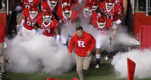 Greg Schiano leads his Rutgers Scarlet Knights onto the field.