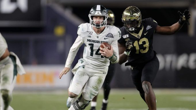 NEW YORK, NY - DECEMBER 27: Quarterback Brian Lewerke #14 of the Michigan State Spartans rushes past defensive lineman Manny Walker #13 of the Wake Forest Demon Deacons during the second half of the New Era Pinstripe Bowl at Yankee Stadium on December 27, 2019 in the Bronx borough of New York City. Michigan State Spartans won 27-21.