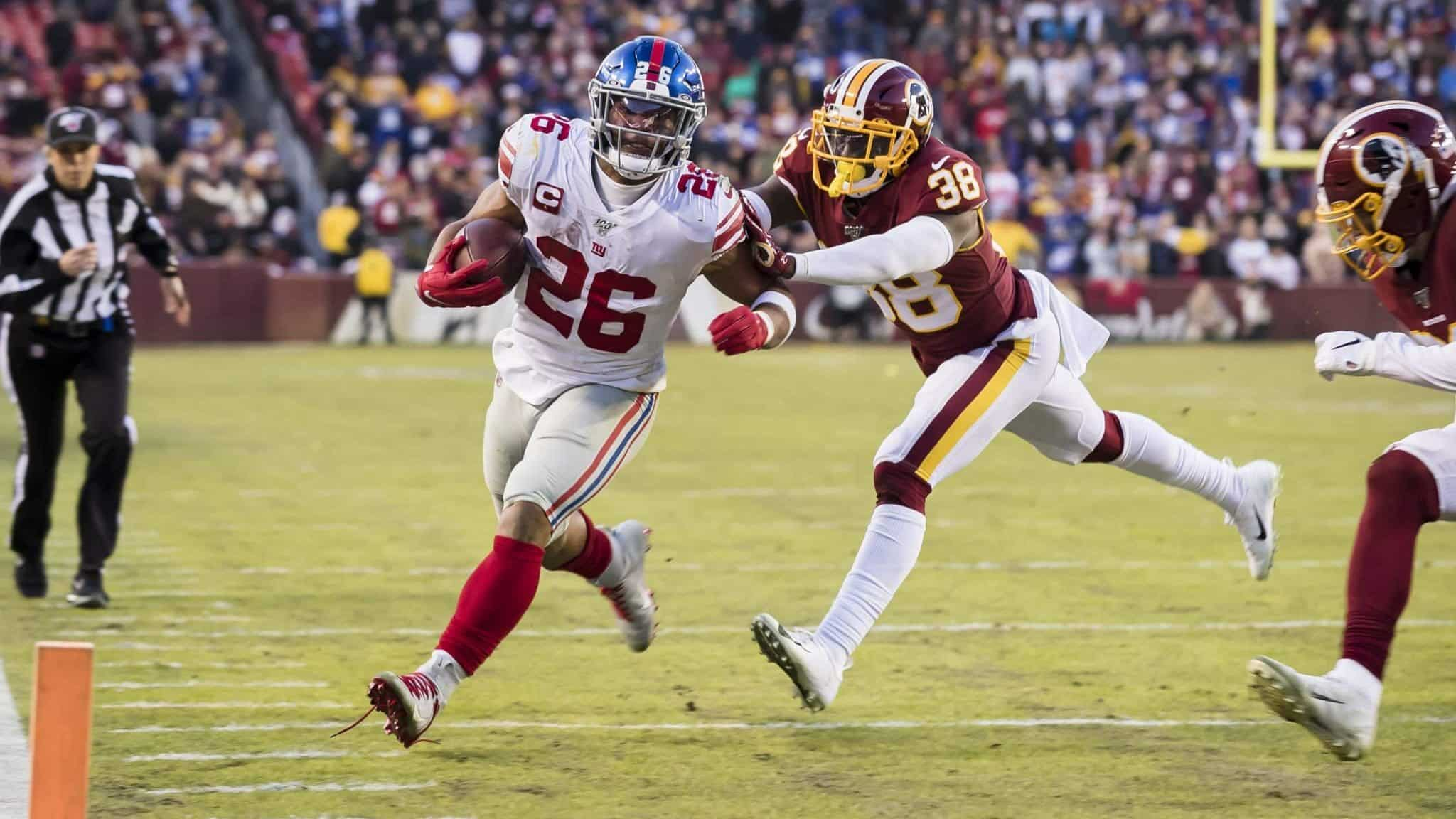 LANDOVER, MD - DECEMBER 22: Saquon Barkley #26 of the New York Giants is shoved out of bounds by Kayvon Webster #38 of the Washington Redskins during overtime at FedExField on December 22, 2019 in Landover, Maryland.