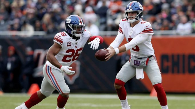 CHICAGO, ILLINOIS - NOVEMBER 24: Daniel Jones #8 of the New York Giants hands the ball off to Saquon Barkley #26 in the second quarter against the Chicago Bears at Soldier Field on November 24, 2019 in Chicago, Illinois.