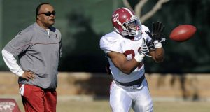 Alabama running back Mark Ingram makes a catch as associate head and running backs coach Burton Burns looks on during practice, Saturday, Jan. 2, 2010, in Costa Mesa, Calif., in preparation for their BCS Championship NCAA college football game against Texas. The game is scheduled for Thursday, Jan. 7.