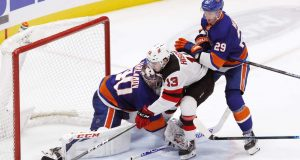 New York Islanders center Brock Nelson (29) watches as New Jersey Devils center Nico Hischier (13) tips the puck in past Islanders goaltender Semyon Varlamov (40) for a go-ahead goal during the third period of an NHL hockey game, Thursday, Jan. 2, 2020, in Uniondale, N.Y.