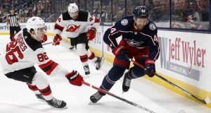 Columbus Blue Jackets defenseman Vladislav Gavrikov, right, of Russia, chases the puck in front of New Jersey forward Jack Hughes, left, and forward Miles Wood Devils during the second period an NHL hockey game in Columbus, Ohio, Saturday, Jan. 18, 2020.