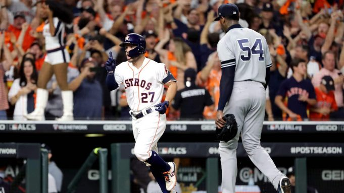HOUSTON, TEXAS - OCTOBER 19: Jose Altuve #27 of the Houston Astros comes home to score following his ninth inning walk-off two-run home run as Aroldis Chapman #54 of the New York Yankees walks off the field in game six of the American League Championship Series at Minute Maid Park on October 19, 2019 in Houston, Texas. The Astros defeated the Yankees 6-4.