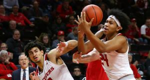 PISCATAWAY, NJ - JANUARY 09: Ron Harper Jr. #24 of the Rutgers Scarlet Knights grabs a rebound with help from teammate Geo Baker #0 against Kyle Young #25 of the Ohio State Buckeyes during the first half a game at Rutgers Athletic Center on January 9, 2019 in Piscataway, New Jersey.