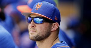 PORT ST. LUCIE, FLORIDA - FEBRUARY 23: Tim Tebow #15 of the New York Mets looks on in the dugout against the Atlanta Braves during the Grapefruit League spring training game at First Data Field on February 23, 2019 in Port St. Lucie, Florida.