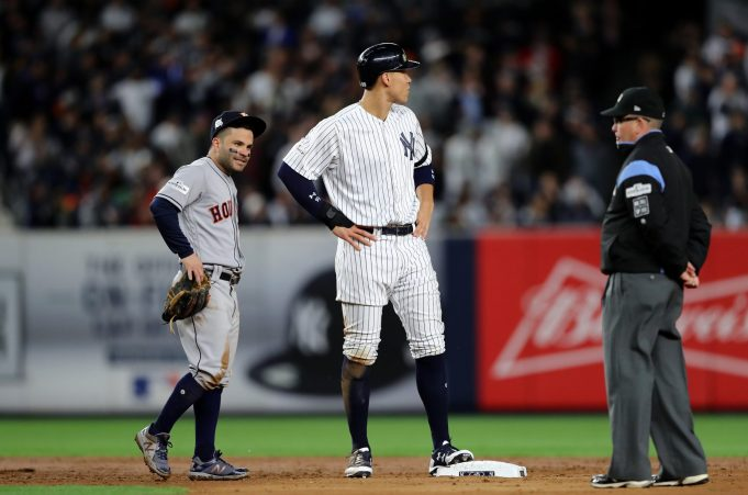 NEW YORK, NY - OCTOBER 16: Jose Altuve #27 of the Houston Astros and Aaron Judge #99 of the New York Yankees look on during the third inning in Game Three of the American League Championship Series at Yankee Stadium on October 16, 2017 in the Bronx borough of New York City.