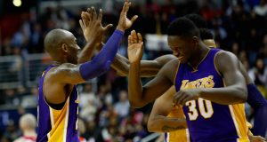 WASHINGTON, DC - DECEMBER 02: Kobe Bryant #24 of the Los Angeles Lakers celebrates with Julius Randle #30 during a timeout in the second half against the Washington Wizards at Verizon Center on December 2, 2015 in Washington, DC. NOTE TO USER: User expressly acknowledges and agrees that, by downloading and or using this photograph, User is consenting to the terms and conditions of the Getty Images License Agreement.
