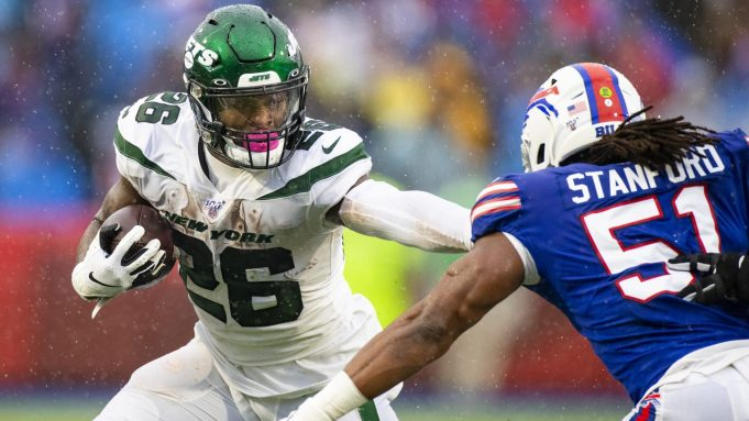 ORCHARD PARK, NY - DECEMBER 29: Le'Veon Bell #26 of the New York Jets delivers a stiff arm against Julian Stanford #51 of the Buffalo Bills during the second quarter at New Era Field on December 29, 2019 in Orchard Park, New York.