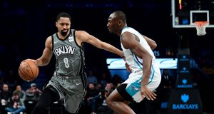 NEW YORK, NEW YORK - DECEMBER 11: Spencer Dinwiddie #8 of the Brooklyn Nets drives past Bismack Biyombo #8 of the Charlotte Hornets during the first half at Barclays Center on December 11, 2019 in New York City. NOTE TO USER: User expressly acknowledges and agrees that, by downloading and or using this photograph, User is consenting to the terms and conditions of the Getty Images License Agreement.