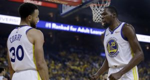 Golden State Warriors' Kevin Durant, right, speaks with Stephen Curry (30) after Curry was called for a foul during the first half of Game 5 of the team's second-round NBA basketball playoff series against the Houston Rockets on Wednesday, May 8, 2019, in Oakland, Calif.