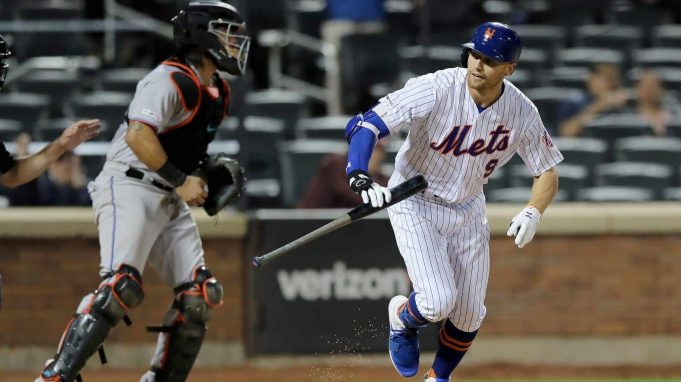 NEW YORK, NEW YORK - SEPTEMBER 24: Brandon Nimmo #9 of the New York Mets heads to first after he is walked with the bases loaded to score the game winning run in the 11th inning as catcher Jorge Alfaro #38 of the Miami Marlins reacts at Citi Field on September 24, 2019 in the Flushing neighborhood of the Queens borough of New York City.The New York Mets defeated the Miami Marlins 5-4 in 11 innings.