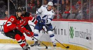 NEWARK, NEW JERSEY - JANUARY 12: Ondrej Palat #18 of the Tampa Bay Lightning clears the puck away from Nico Hischier #13 and P.K. Subban #76 of the New Jersey Devils during the first period at Prudential Center on January 12, 2020 in Newark, New Jersey.