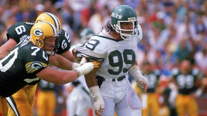 AUGUST 27: Defensive end Mark Gastineau #99 of the New York Jets gets held by a Green Bay Packers linemen during a preaseson game on August 27, 1988.