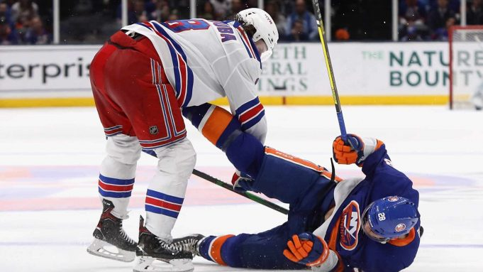 NEW YORK, NEW YORK - FEBRUARY 25: Jacob Trouba #8 of the New York Rangers checks Michael Dal Colle #28 of the New York Islanders during the third period at NYCB Live's Nassau Coliseum on February 25, 2020 in Uniondale, New York. The Rangers defeated the Islanders 4-3 in overtime.