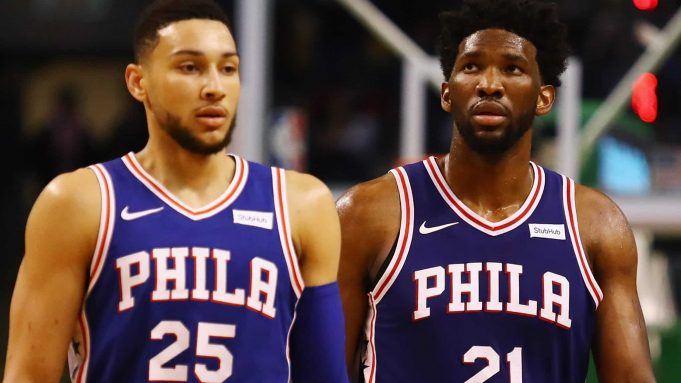 BOSTON, MA - JANUARY 18: Ben Simmons #25 and Joel Embiid #21 of the Philadelphia 76ers walk off the court during a time out in the second half against the Boston Celtics at TD Garden on January 18, 2018 in Boston, Massachusetts.