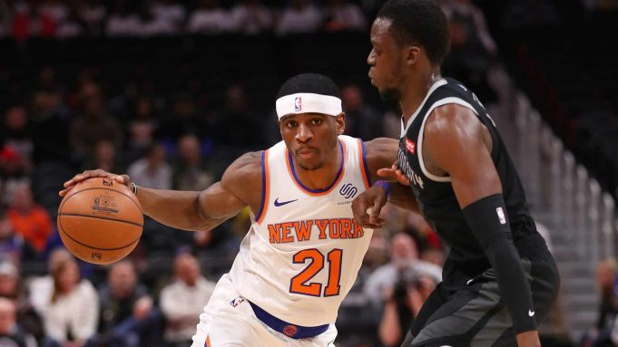DETROIT, MICHIGAN - FEBRUARY 08: Damyean Dotson #21 of the New York Knicks tries to drive around Reggie Jackson #1 of the Detroit Pistons during the first half at Little Caesars Arena on February 08, 2019 in Detroit, Michigan. NOTE TO USER: User expressly acknowledges and agrees that, by downloading and or using this photograph, User is consenting to the terms and conditions of the Getty Images License Agreement.