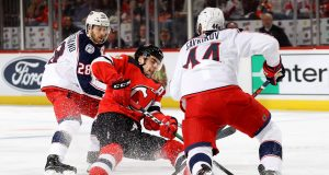 NEWARK, NEW JERSEY - FEBRUARY 16: Will Butcher #8 of the New Jersey Devils is tripped up as Oliver Bjorkstrand #28 and Vladislav Gavrikov #44 of the Columbus Blue Jackets defend at Prudential Center on February 16, 2020 in Newark, New Jersey.