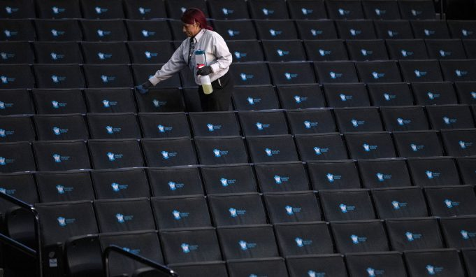 NEW YORK, NEW YORK - MARCH 12: A worker disinfects seats prior to the start of the second round of the 2020 Atlantic 10 men's basketball tournament at Barclays Center on March 12, 2020 in the Brooklyn borough of New York City. The tournament was canceled amid growing concerns of the spread of Coronavirus (COVID-19).