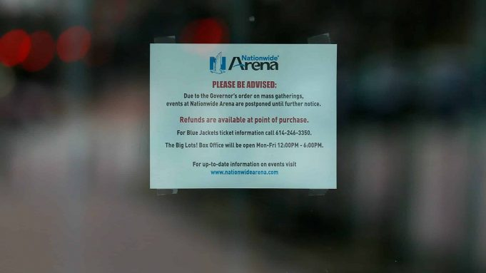 COLUMBUS, OH - MARCH 12: A sign posted on an entrance door to Nationwide Arena alerts fans that all events at the arena have been postponed on March 12, 2020 in Columbus, Ohio. The game between the Columbus Blue Jackets and the Pittsburgh Penguins was canceled after the NHL's decision to suspend the remaining games in the season due to the continuing outbreak of the coronavirus (COVID-19).