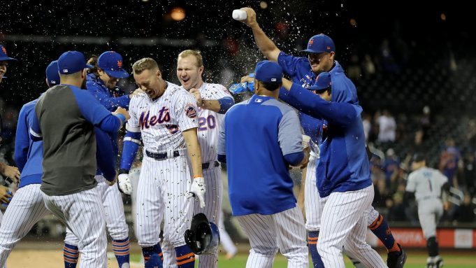NEW YORK, NEW YORK - SEPTEMBER 24: Brandon Nimmo #9 of the New York Mets is congratulated by teammates as Pete Alonso #20 pulls at his jersey after Nimmo scored the game winning run with a bases loaded walk at Citi Field on September 24, 2019 in the Flushing neighborhood of the Queens borough of New York City.The New York Mets defeated the Miami Marlins 5-4 in 11 innings.