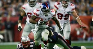 GLENDALE, AZ - FEBRUARY 03: Running back Ahmad Bradshaw #44 of the New York Giants carries the football through the New England Patriots defense in the second quarter during Super Bowl XLII on February 3, 2008 at the University of Phoenix Stadium in Glendale, Arizona.