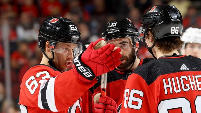 NEWARK, NEW JERSEY - FEBRUARY 08: Jesper Bratt #63 of the New Jersey Devils talks with teammates Kyle Palmieri #21 and Jack Hughes #86 of the New Jersey Devils in the second period against the Los Angeles Kings at Prudential Center on February 08, 2020 in Newark, New Jersey.