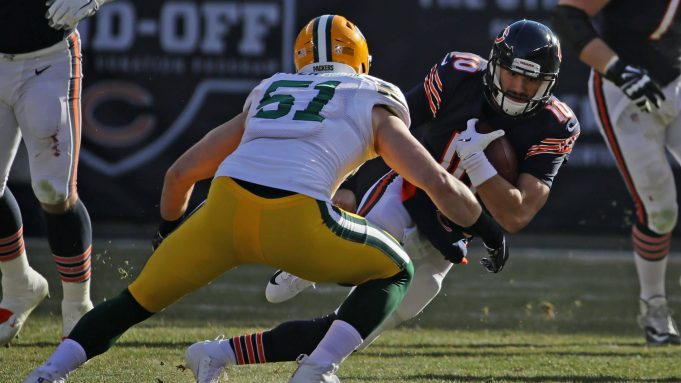 CHICAGO, IL - DECEMBER 16: Quarterback Mitchell Trubisky #10 of the Chicago Bears carries the football against Kyler Fackrell #51 of the Green Bay Packers in the second quarter at Soldier Field on December 16, 2018 in Chicago, Illinois.