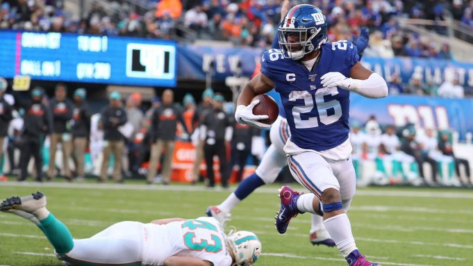 EAST RUTHERFORD, NEW JERSEY - DECEMBER 15: Saquon Barkley #26 of the New York Giants scores a touchdown in the third quarter against the Miami Dolphins during their game at MetLife Stadium on December 15, 2019 in East Rutherford, New Jersey.