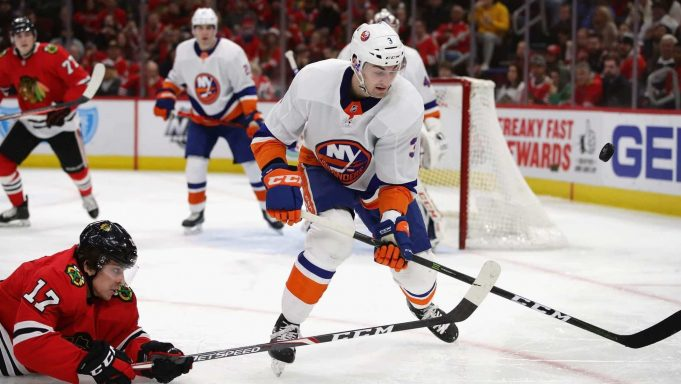 CHICAGO, ILLINOIS - DECEMBER 27: Dylan Strome #17 of the Chicago Blackhawks hits the ice as he knocks the puck away from Adam Pelech #3 of the New York Islanders at the United Center on December 27, 2019 in Chicago, Illinois.