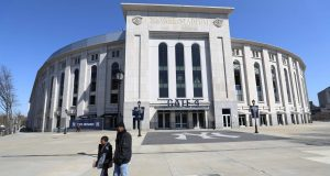 """BRONX, NEW YORK - MARCH 26: A father and son walk past a closed Yankee Stadium on the scheduled date for Opening Day March 26, 2020 in the Bronx, New York. Major League Baseball has postponed the start of its season due to the coronavirus (COVID-19) outbreak and MLB commissioner Rob Manfred recently said the league is """"probably not gonna be able to"""" play a full 162-game regular season."""
