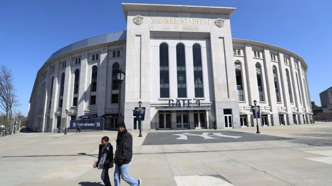 BRONX, NEW YORK - MARCH 26: A father and son walk past a closed Yankee Stadium on the scheduled date for Opening Day March 26, 2020 in the Bronx, New York. Major League Baseball has postponed the start of its season due to the coronavirus (COVID-19) outbreak and MLB commissioner Rob Manfred recently said the league is