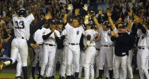 21 Oct 2001: Alfonso Soriano of the New York Yankees is met by his teammates at home plate after hitting the game winning home run against Kazuhiro Sasaki of the Seattle Mariners in game four of the American League Championship Series at Yankee Stadium, in the Bronx, New York.