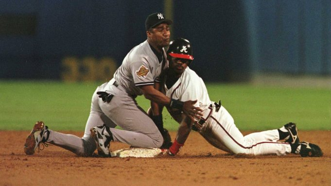 23 Oct 1996: Marquis Grissom of the Atlanta Braves dives safely into base and Mariano Duncan of the New York Yankees after hitting a 2 RBI double in the second inning of game four of the World Series at Fulton County Stadium in Atlanta, Georgia.