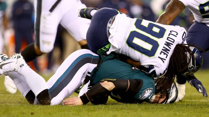 PHILADELPHIA, PENNSYLVANIA - JANUARY 05: Quarterback Carson Wentz #11 of the Philadelphia Eagles is hit by Jadeveon Clowney #90 of the Seattle Seahawks during the NFC Wild Card Playoff game at Lincoln Financial Field on January 05, 2020 in Philadelphia, Pennsylvania.