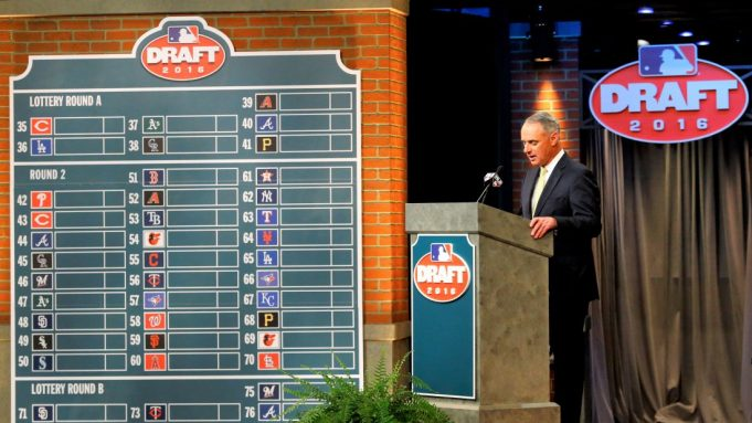 FILE - In this June 9, 2016, file photo, Major League BaseballCommissioner Rob Manfred speaks during the MLB draft, in Secaucus, N.J. Major League Baseball will cuts its amateur draft from 40 rounds to five this year, a move that figures to save teams about $30 million. Clubs gained the ability to reduce the draft as part of their March 26 agreement with the players' association and MLB plans to finalize a decision next week to go with the minimum, a person familiar with the decision told The Associated Press. The person spoke Friday, May 8, 2020, on condition of anonymity because no decision was announced.
