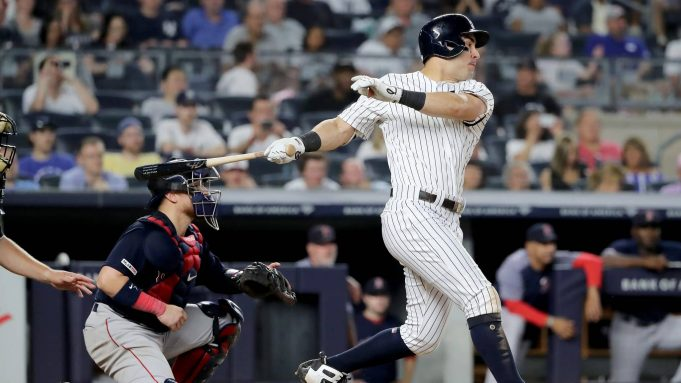 NEW YORK, NEW YORK - AUGUST 03: Mike Tauchman #39 of the New York Yankees hits a 2 RBI single in the seventh inning as Christian Vazquez #7 of the Boston Red Sox defends during game two of a double header at Yankee Stadium on August 03, 2019 in New York City.