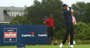 HOBE SOUND, FLORIDA - MAY 24: NFL player Tom Brady of the Tampa Bay Buccaneers plays his shot from the first tee as Tiger Woods an former NFL player Peyton Manning look on during The Match: Champions For Charity at Medalist Golf Club on May 24, 2020 in Hobe Sound, Florida.