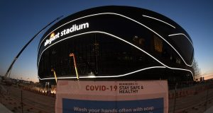 LAS VEGAS, NEVADA - APRIL 23: (EDITORS NOTE: This image was shot with a fisheye lens.) A sign with guidelines for how to stay safe from the coronavirus is posted on a fence while crews test out architectural light ribbons and exterior sign lighting as construction continues at Allegiant Stadium, the USD 2 billion, glass-domed future home of the Las Vegas Raiders on April 23, 2020 in Las Vegas, Nevada. The Raiders and the UNLV Rebels football teams are scheduled to begin play at the 65,000-seat facility in their 2020 seasons. The World Health Organization declared the coronavirus (COVID-19) a pandemic on March 11th.