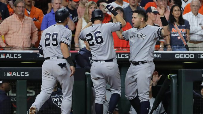 HOUSTON, TEXAS - OCTOBER 19: DJ LeMahieu #26 of the New York Yankees is congratulated by his teammates Gio Urshela #29 and Gary Sanchez #24 after his game-tying two-run home run against the Houston Astros during the ninth inning in game six of the American League Championship Series at Minute Maid Park on October 19, 2019 in Houston, Texas.