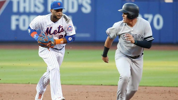 NEW YORK, NEW YORK - JULY 03: Robinson Cano #24 of the New York Mets runs down Gio Urshela #29 of the New York Yankees in the second inning to complete a double play during their game at Citi Field on July 03, 2019 in New York City.